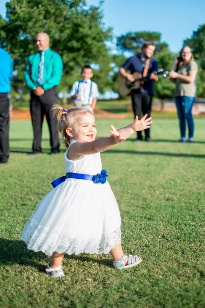 A photo of a bride's daughter smiling and reaching out for her. Photo taken by Pait Photography, at a wedding at Beau Rivage Golf and Resort, in Wilmington, NC