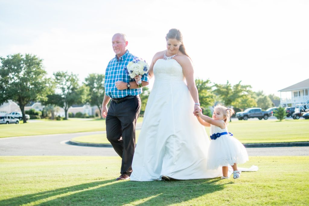 A photo of a bride being walked by her father and daughter to her wedding ceremony.