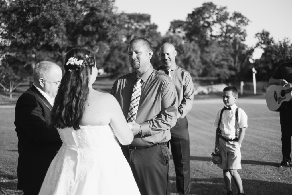 A black and white photo of a bride and groom holding hands during their wedding ceremony.