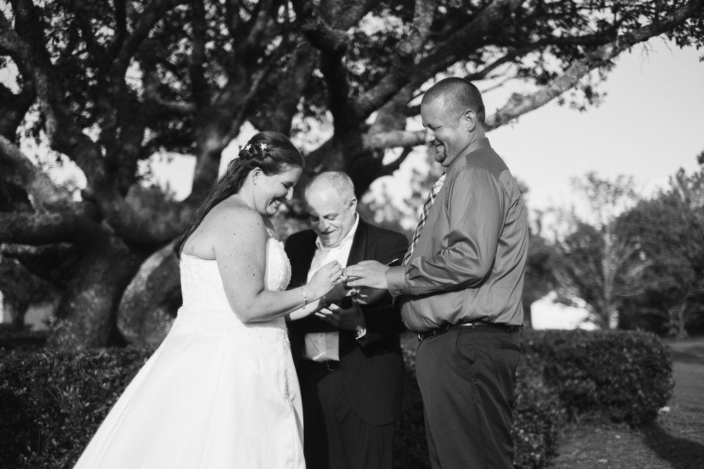 A black and white photo of a bride and groom laughing while they exchange wedding rings, during their ceremony.  Photo taken by Pait Photography, at a wedding at Beau Rivage Golf and Resort, in Wilmington, NC