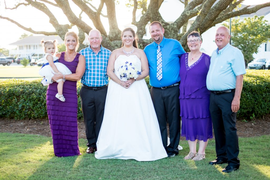 A photo of a bride and groom, and their family, after their wedding ceremony. Photo taken by Pait Photography, at a wedding at Beau Rivage Golf and Resort, in Wilmington, NC