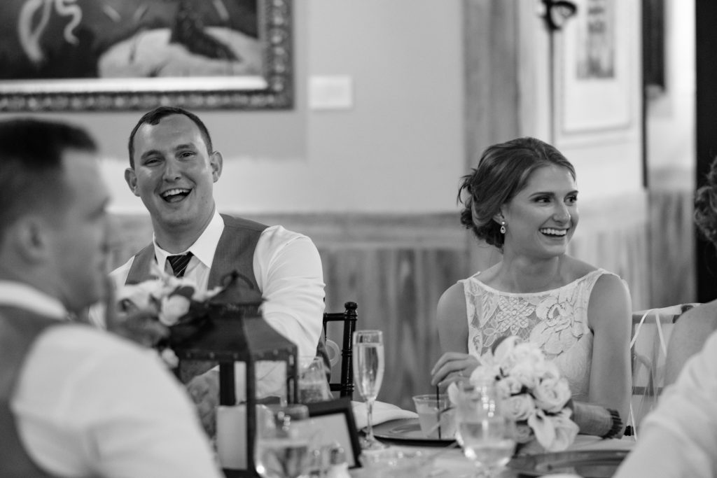 A black and white candid photo of a bride and groom laughing during their reception.