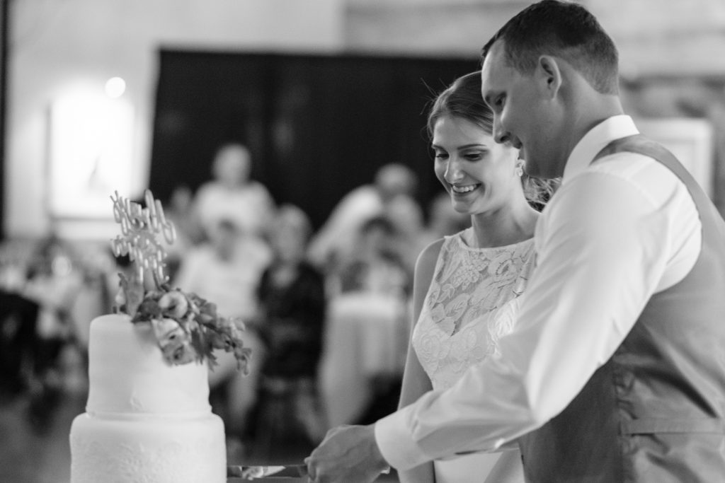 A black and white candid photo of a bride and groom smiling, and cutting their wedding cake together.