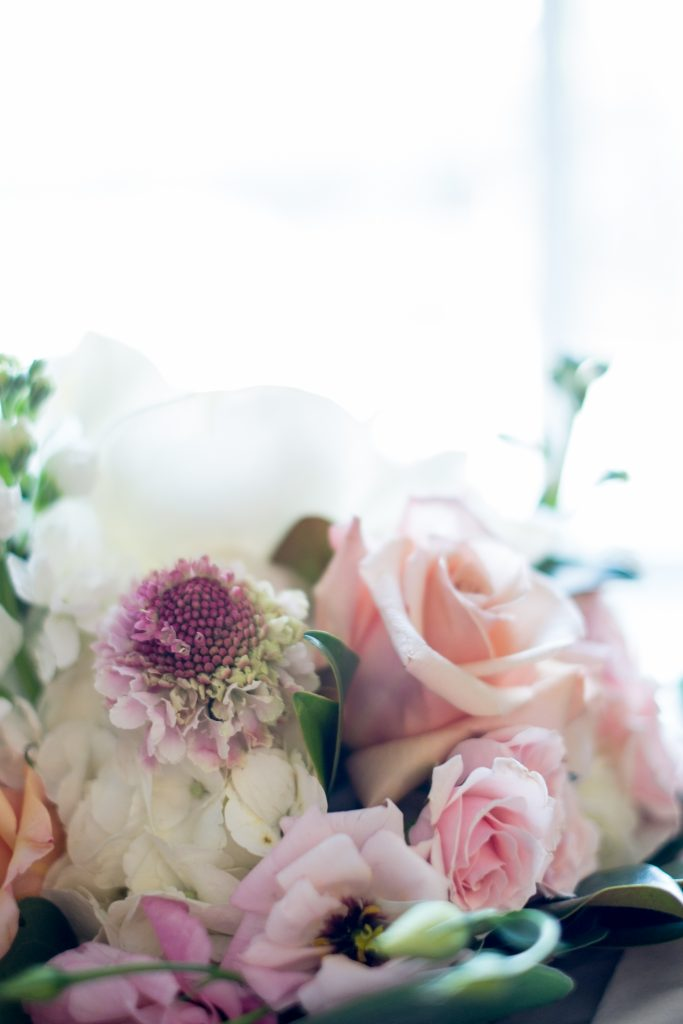 A photo of a bride's wedding bouquet, taken at a hotel during pre-ceremony, wedding preparations. Photo taken by Pait Photography, at a wedding at hotel in Raleigh, NC