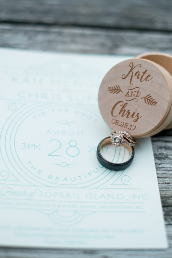 A detail photo of a the bride and groom's wedding rings, placed against their engraved, wooden ring box, and invitation.