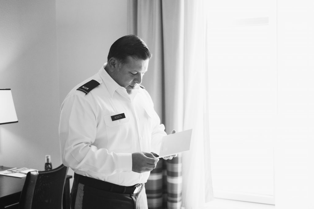 A black and white photo of a groom before his wedding, reading a card from his fiancée. Photo taken by Pait Photography, at a hotel, in Raleigh, NC.