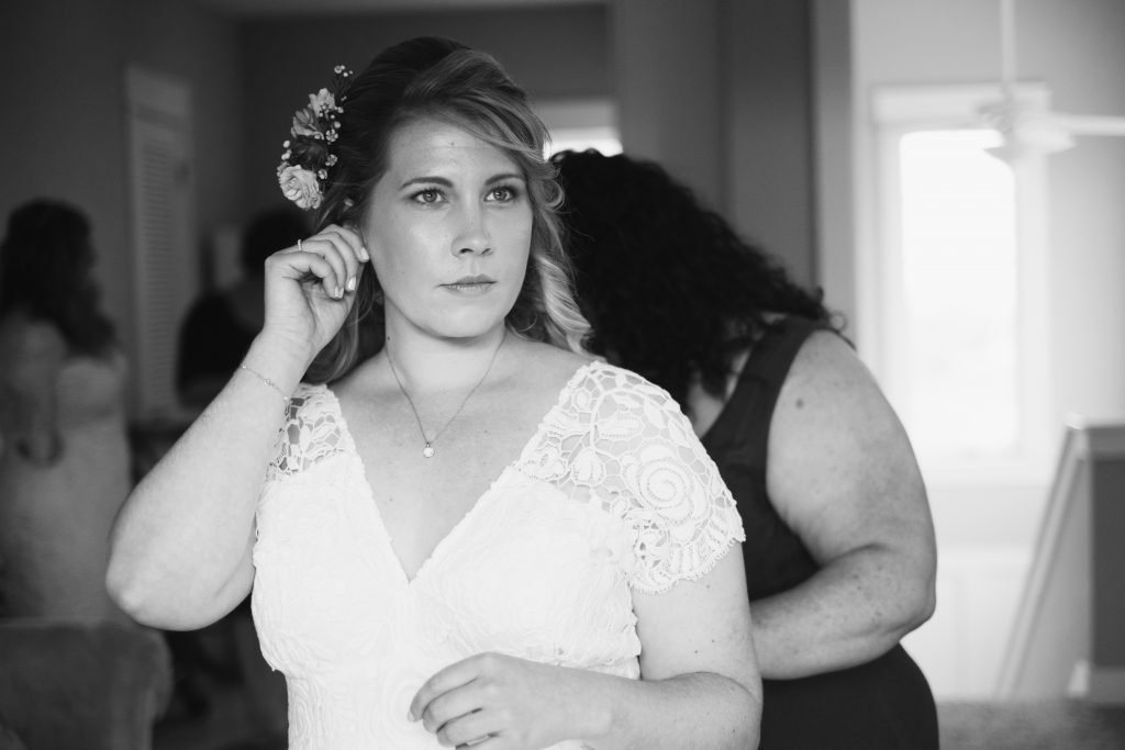 A black and white photo of a bride putting on her earrings before her wedding.