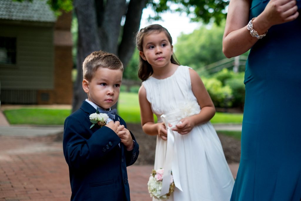 A photo of a ring bearer and flower girl, looking on towards the bride and wedding chapel, before the wedding ceremony. Photo taken by Pait Photography, at a wedding at St. Mark's Chapel, at the Mordecai Historic Park, in Raleigh, NC.