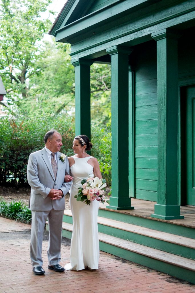A photo of the bride and her father, outside, arm in arm and smiling at each other, before he walks her to the wedding chapel. Photo taken by Pait Photography, at a wedding at St. Mark's Chapel, at the Mordecai Historic Park, in Raleigh, NC.