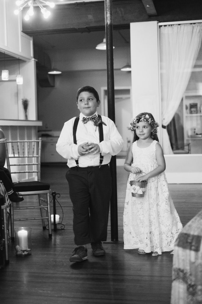 A black and white photo of a ring bearer and flower girl, walking down the aisle at a wedding ceremony. Photo taken by Pait Photography, at a wedding at The Loft on Front, in Wilmington, NC.