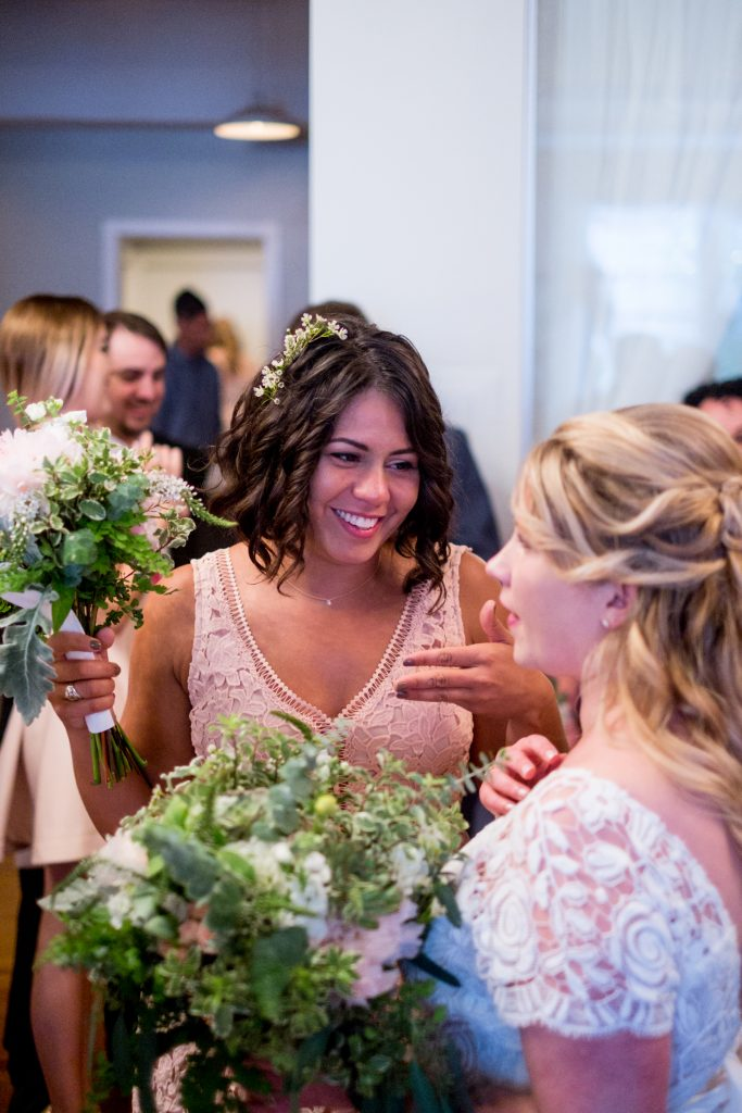 A photo of a the Maid of Honor, smiling and talking to the bride, after a wedding ceremony.