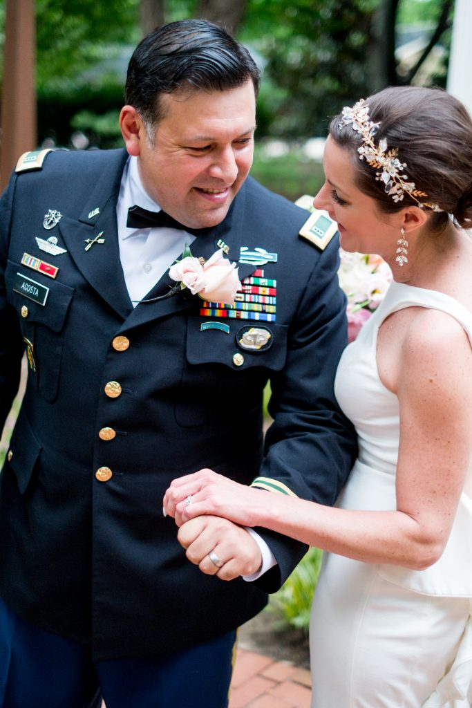 A photo of of the bride and groom, after their wedding ceremony, hand in hand, smiling at each other. Photo taken by Pait Photography, at a wedding at St. Mark's Chapel, at the Mordecai Historic Park, in Raleigh, NC.