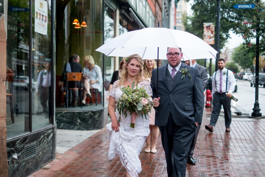 A photo of a bride and groom walking together underneath a white umbrella, with their wedding party walking behind them, in downtown Wilmington, NC.
