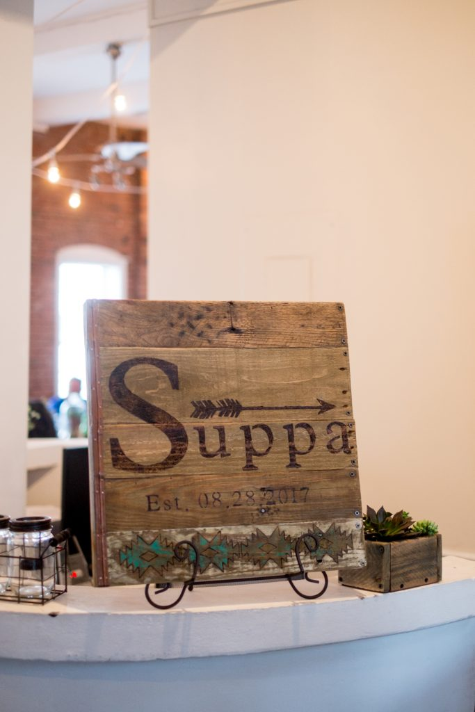 A detail photo of a handmade, wooden decoration with the couple's last name painted on it. Photo taken by Pait Photography, at a wedding at The River Room, in Wilmington, NC.