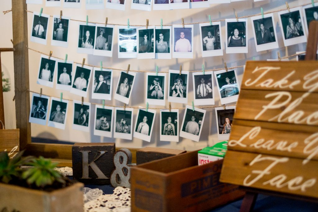 A detail photo of decorations and a Polaroid photo station for wedding guests. Photo taken by Pait Photography, at a wedding at The River Room, in Wilmington, NC.
