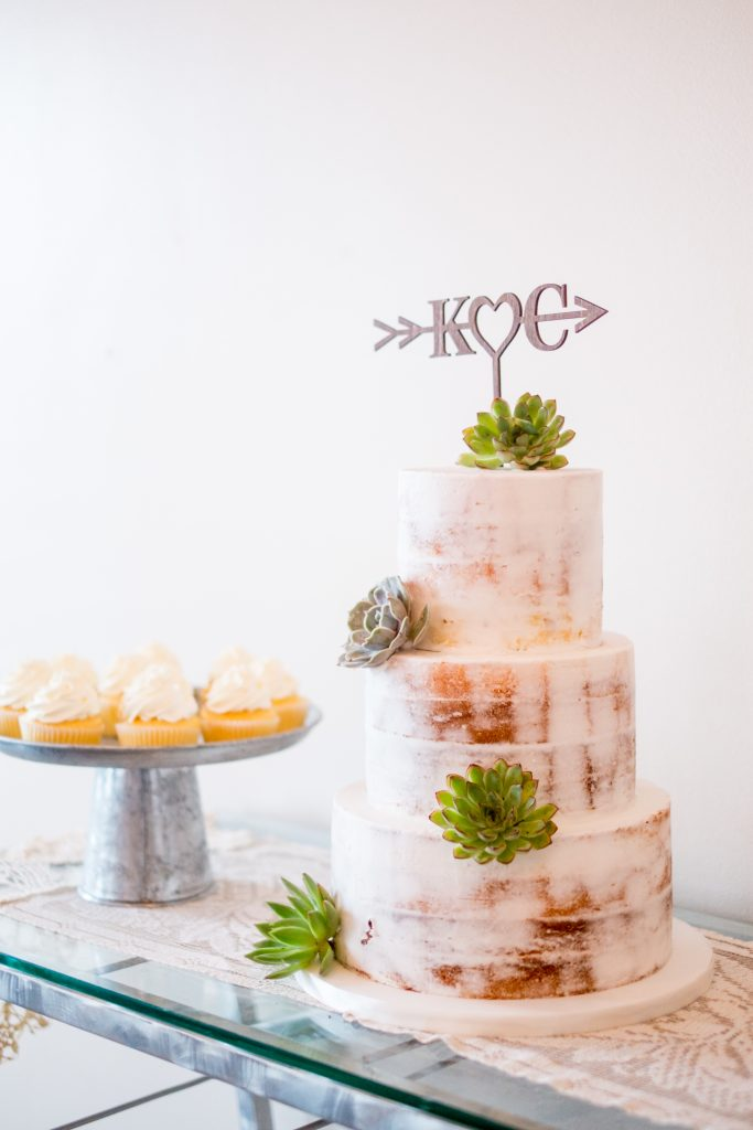 A photo of a naked wedding cake, decorated with faux succulent plants.