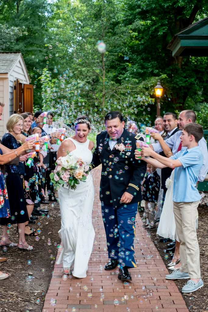 A photo of the bride and groom exiting after their wedding ceremony, in the midst of a send-off of bubbles, put on by their guests. Photo taken by Pait Photography, at a wedding at St. Mark's Chapel, at the Mordecai Historic Park, in Raleigh, NC.