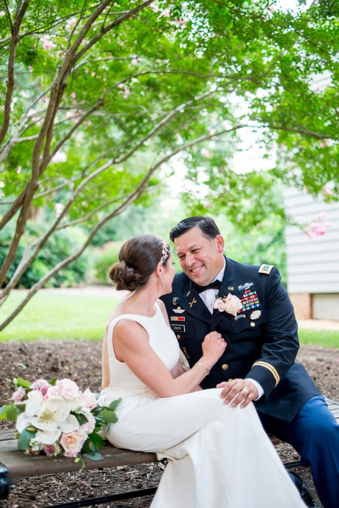 A photo of of the bride and groom, after their wedding ceremony, sitting under a tree, smiling at each other. Photo taken by Pait Photography, at a wedding at St. Mark's Chapel, at the Mordecai Historic Park, in Raleigh, NC.