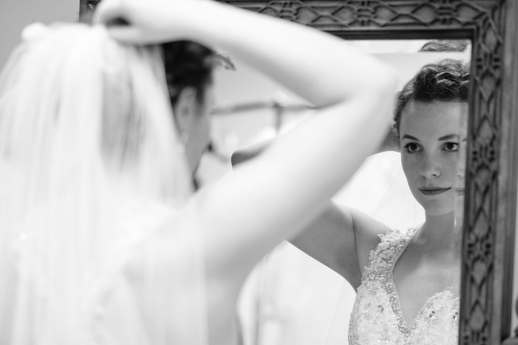 A black and white photo of a bride in her wedding dress, looking in a mirror.