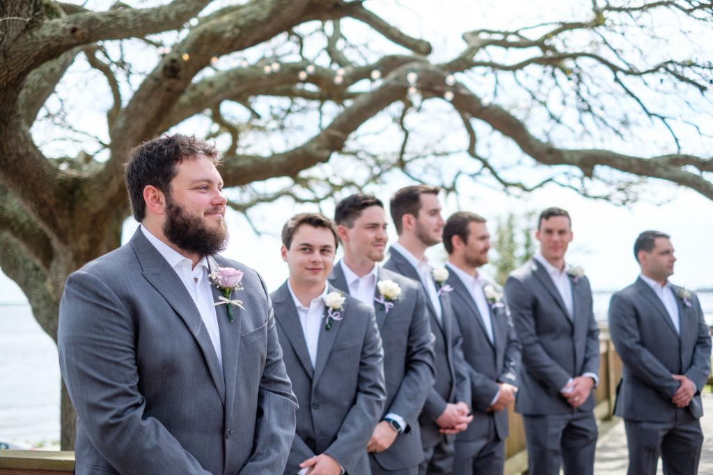 A portrait of a groom reacting to seeing the bride walking down the aisle, during their wedding ceremony,