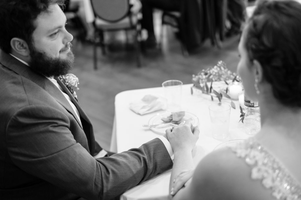 A black and white photo of a groom and bride holding hands, at their sweetheart table.