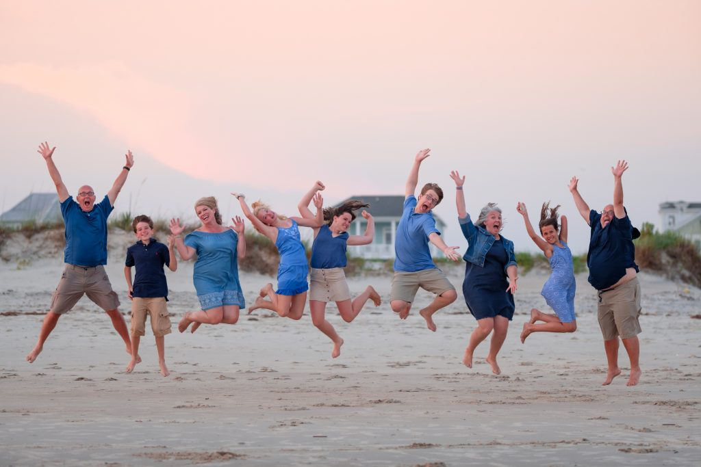 A photo of a family jumping together and smiling, at sunset, on Oak Island, NC