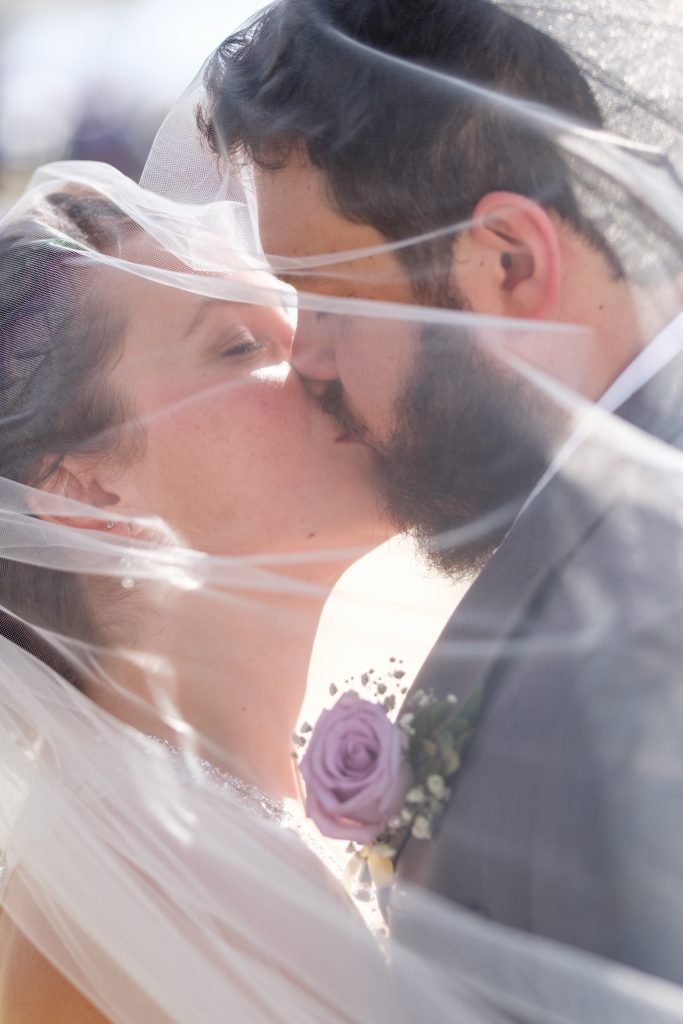 A photo of a bride and groom kissing underneath the bride's wedding veil.
