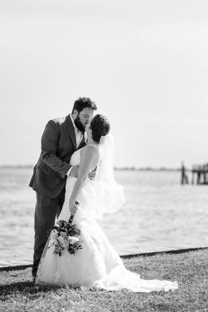 A black and white photo of a bride and groom kissing in front of the water, after their wedding ceremony at the Southport Community Center, in Southport, NC>