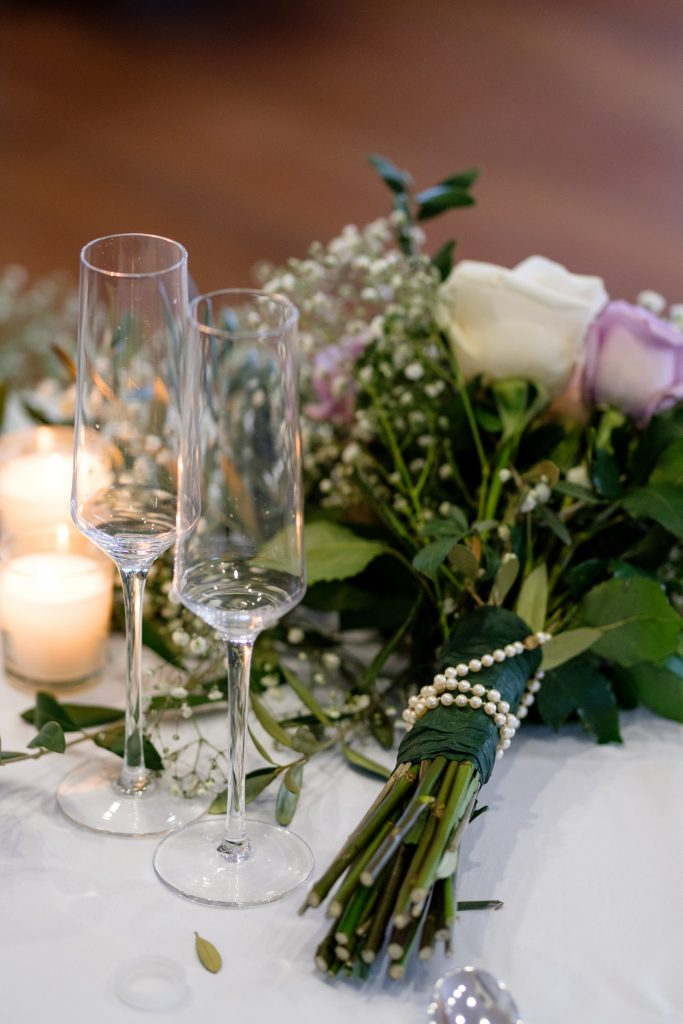 A detail photo of two champagne glasses and the bride's wedding bouquet.