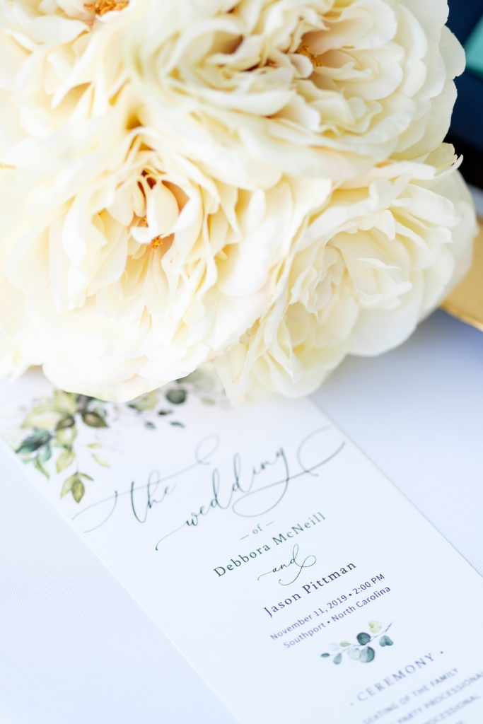 Detail photo of a bridal bouquet and wedding invitation.